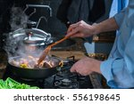 man interferes with the meat in ... | Shutterstock . vector #556198645