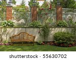 A garden wall with a trellis and red rose bushes. - stock photo