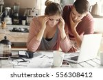 Small photo of Depressed young woman having bad headache holding her temples feeling stressed by lack of money to pay out family debts, her puzzled husband standing next to her, trying to come up with solution
