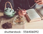a man reading a book with cup... | Shutterstock . vector #556406092