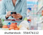 woman doing grocery shopping at ... | Shutterstock . vector #556476112