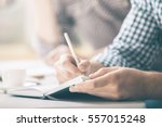 male writing in notepad placed... | Shutterstock . vector #557015248