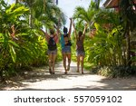 Small photo of Three girls in shorts walking towards the beach with their hands in the air through a sand path surrounded by nature in the island of Koh Phangan, Thailand. Happy young lady friends enjoying vacation