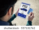 Small photo of man holding a tablet renting a car and a credit card