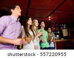 friends holding beer in the bar | Shutterstock . vector #557220955