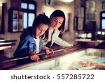 Small photo of Attractive mother and daughter exploring expositions of previous centuries in museum. Focus on the woman