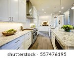 Stock photo white kitchen design features large bar style kitchen island with granite countertop illuminated by 557476195