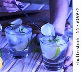 Small photo of A young girl is preparing an alcoholic or non-alcoholic cocktail. hands, bartender, bar, restaurant, mint, lime, lemon, alcoholic, non-alcoholic St.Patrick 's Day, Green background.