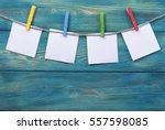 Stock photo clothespin hanging with blank photo papers on wooden background texture 557598085