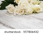 Stock photo white roses on a old white wooden table 557806432