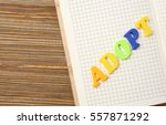 Small photo of Word ADOPT and open notepad on wooden background, closeup