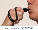 A close up of a coach blowing a whistle - stock photo