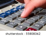 A close up of a man typing on a calculator - stock photo
