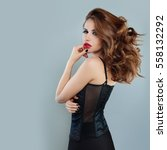 Small photo of Beautiful Alluring Woman with Blowing Hair. Fashion Model in Black Corset