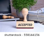 Small photo of Accepted Stamp in the office with binder and notebook in the background