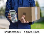 Small photo of Package delivery concept. Man holds cardboard box and payment terminal in hands.