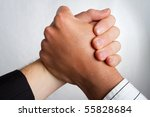 Two caucasian business partners holding hands - stock photo