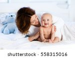 mother and child on a white bed.... | Shutterstock . vector #558315016