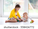 Small photo of Kids playing together at home. Little girl and boy play sitting on the floor next to a window. Toddler child building tower with colorful blocks. Baby starting to crawl. Toys for young children
