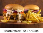 Two Burgers And Fries On Wooden ...