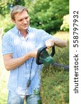 man cutting garden hedge with... | Shutterstock . vector #558797932