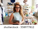 Small photo of Female business owner holding tablet computer in clothes shop
