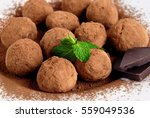 Small photo of Homemade truffle candy sprinkled with cocoa powder, broken dark chocolate and fresh mint on a white plate.