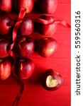 Small photo of Red apples with red ribbon on red background