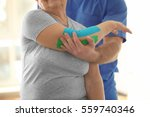 physiotherapist working with... | Shutterstock . vector #559740346