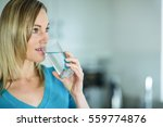 pretty blonde woman drinking a... | Shutterstock . vector #559774876