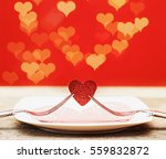 Two Forks Holding Red Heart On...
