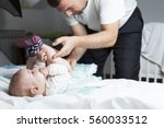 dad changing baby's diapers on... | Shutterstock . vector #560033512