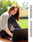 Pretty young woman with a laptop at park. - stock photo