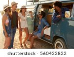 Friends on a road trip hanging out by their camper van - stock photo
