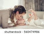Stock photo young mother holding her newborn child mom nursing baby woman and new born boy relax nursery 560474986