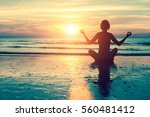 silhouette of a woman yoga on... | Shutterstock . vector #560481412