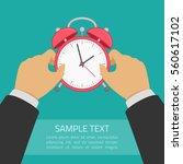 red alarm clock in hand. wake... | Shutterstock .eps vector #560617102