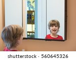 young boy looking at himself in ... | Shutterstock . vector #560645326