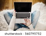 Small photo of top view of a young woman with a computer on her lap