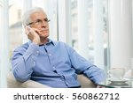 senior businessman sitting at... | Shutterstock . vector #560862712