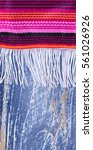 Small photo of Close up of colorful serape with fringe for Cinco de Mayo holiday concept. Vertical layout.