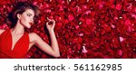 Stock photo valentine s day loving girl the girl in a red dress lying on the floor in the petals of red roses 561162985