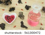 Small photo of Elixir of love, Red philter in heart bowl, finished product in glass bottle and ingredient on bamboo mat.