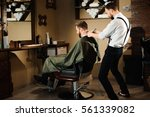 master cuts hair and beard of... | Shutterstock . vector #561339082