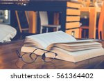 book with glasses on table ... | Shutterstock . vector #561364402