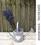 Small photo of Bunch of lavender in a tin watering can on a wooden surface with wood in the background. Bleach effect an space for text.