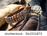 Small photo of Detail of western style ammo belt with buckshot cartridges attached to a saddle with reins and glove in background