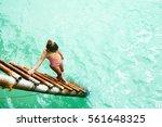 child in swimsuit entering sea... | Shutterstock . vector #561648325