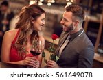 handsome man giving rose to... | Shutterstock . vector #561649078