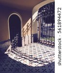 Small photo of Vintage yellow house back door hall with a geometric floor and an arabesque black iron gate, illuminated by sunlight